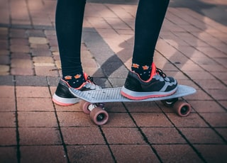 person wearing running shoes using penny board