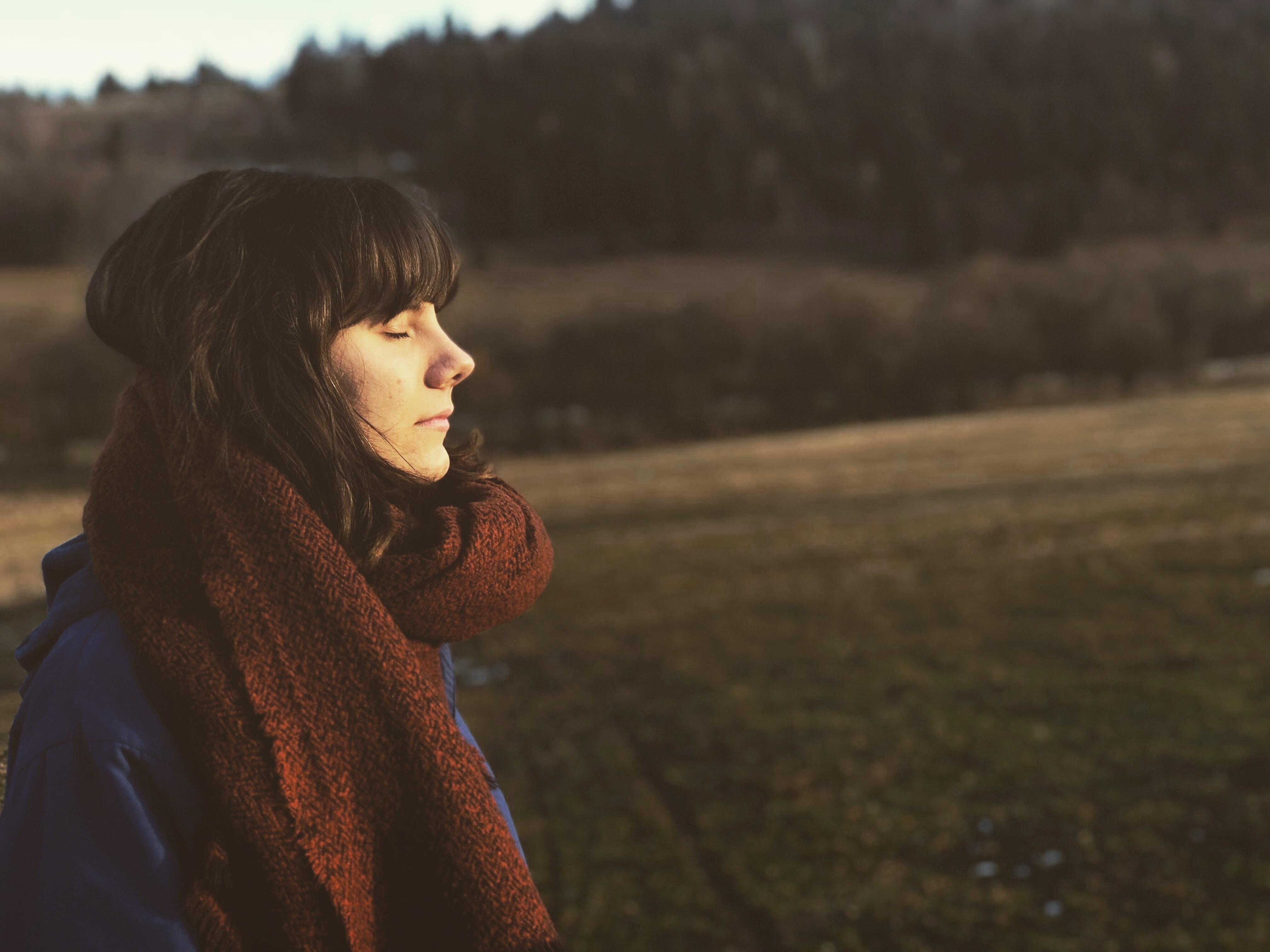 woman close eye standing on grass field