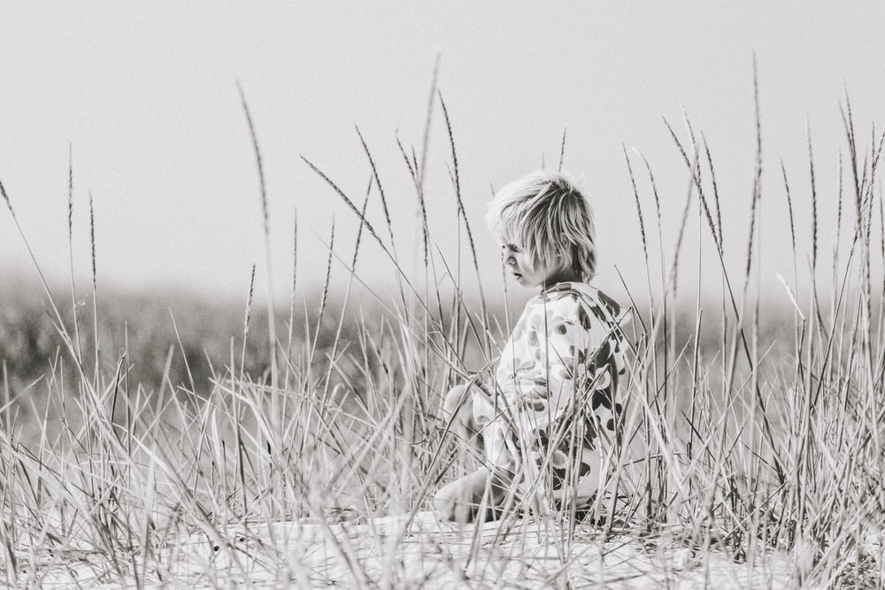 grayscale photo of child sitting