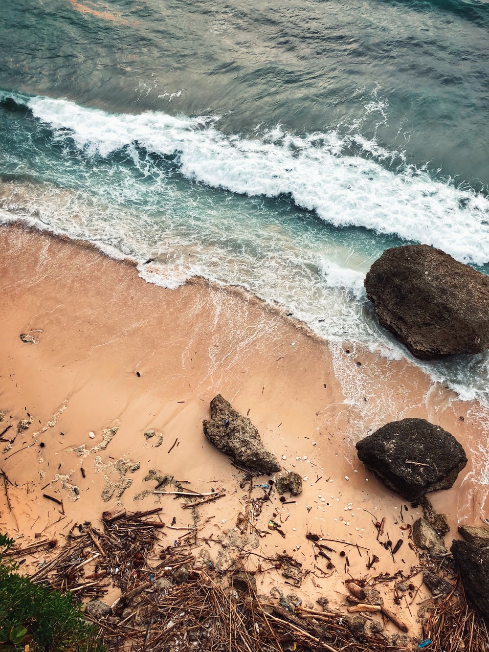 aerial view photography of rocks and wood sticks on shore near ocean during daytime