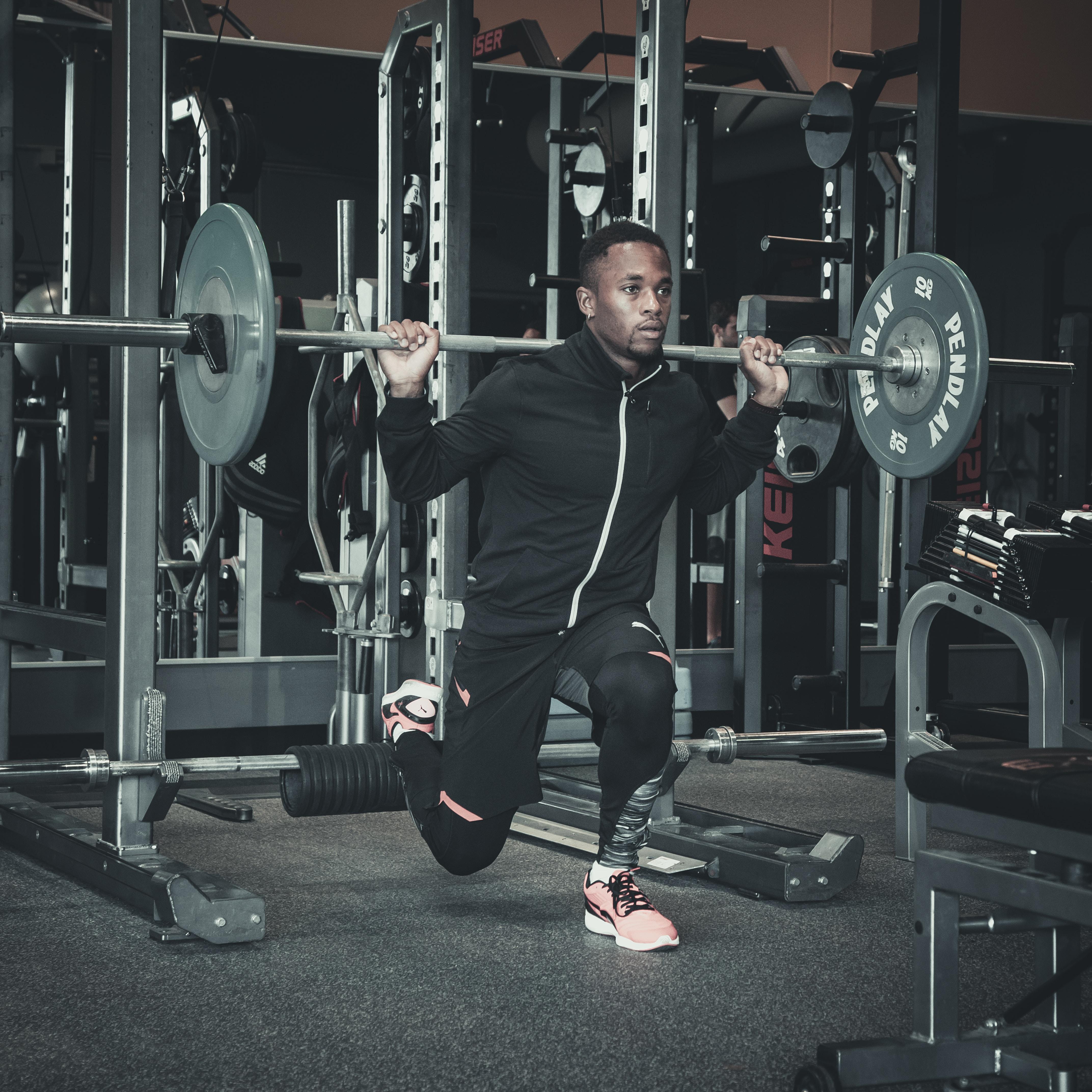 man lifting black barbell