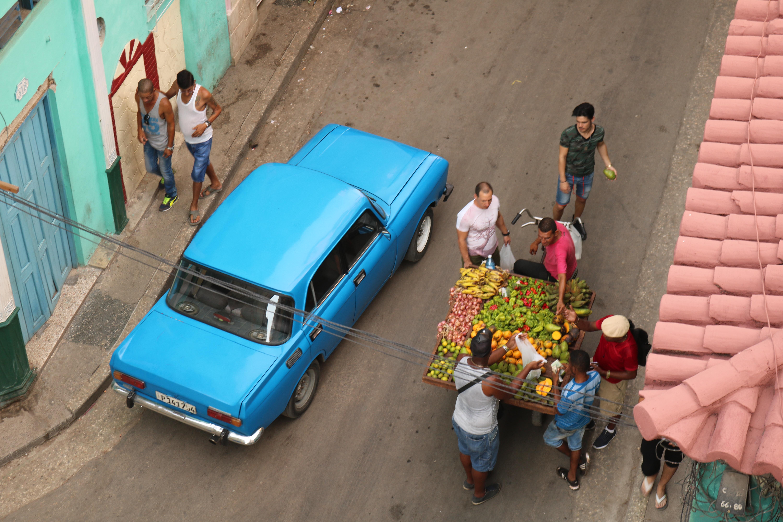 sedan crossing road beside fruit vendor cart
