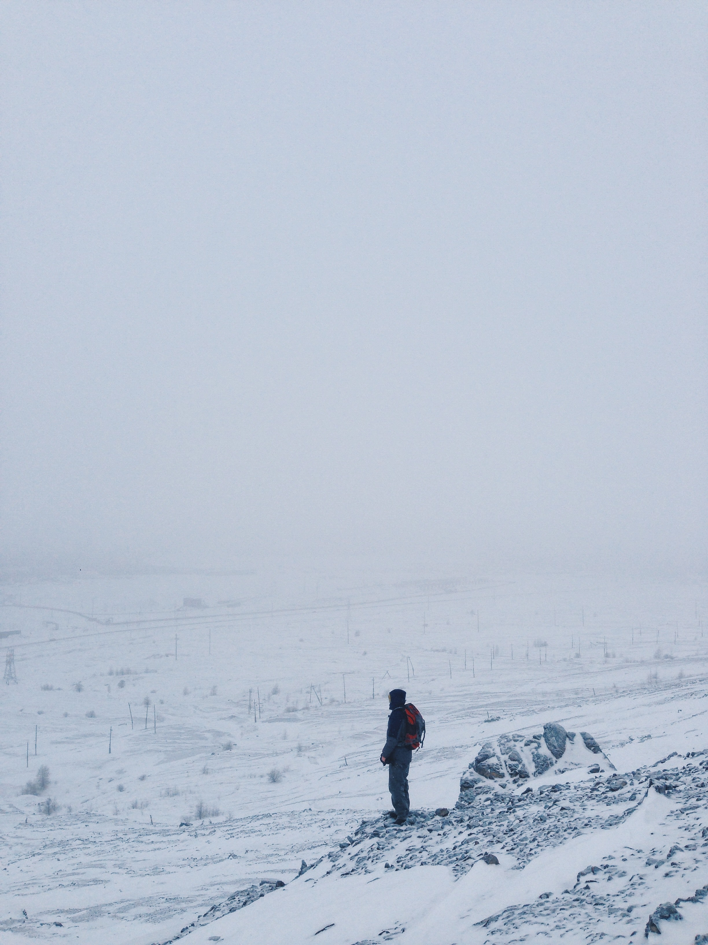 person standing on snow covered cliff