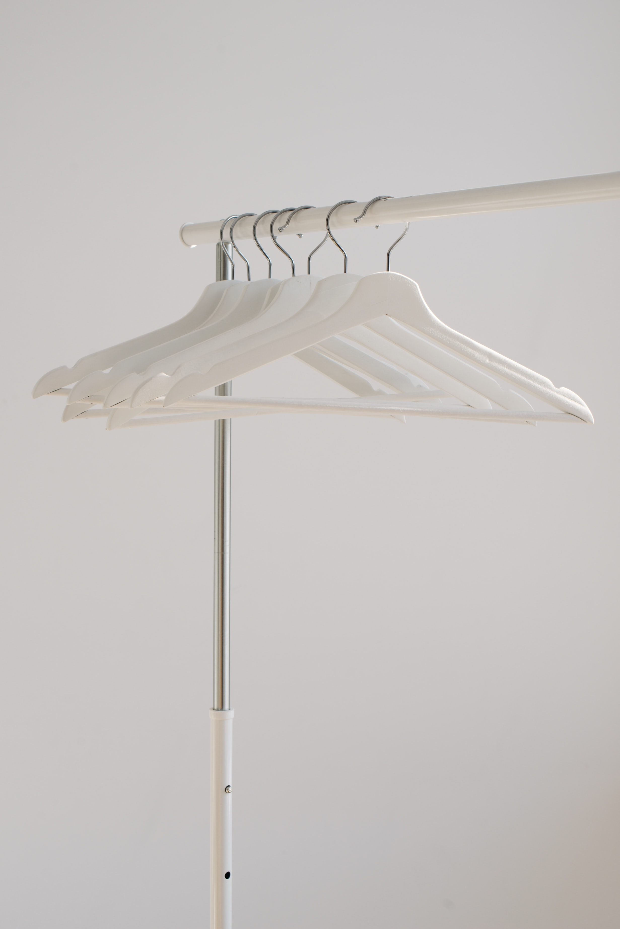 white clothes hangers hanging on rack