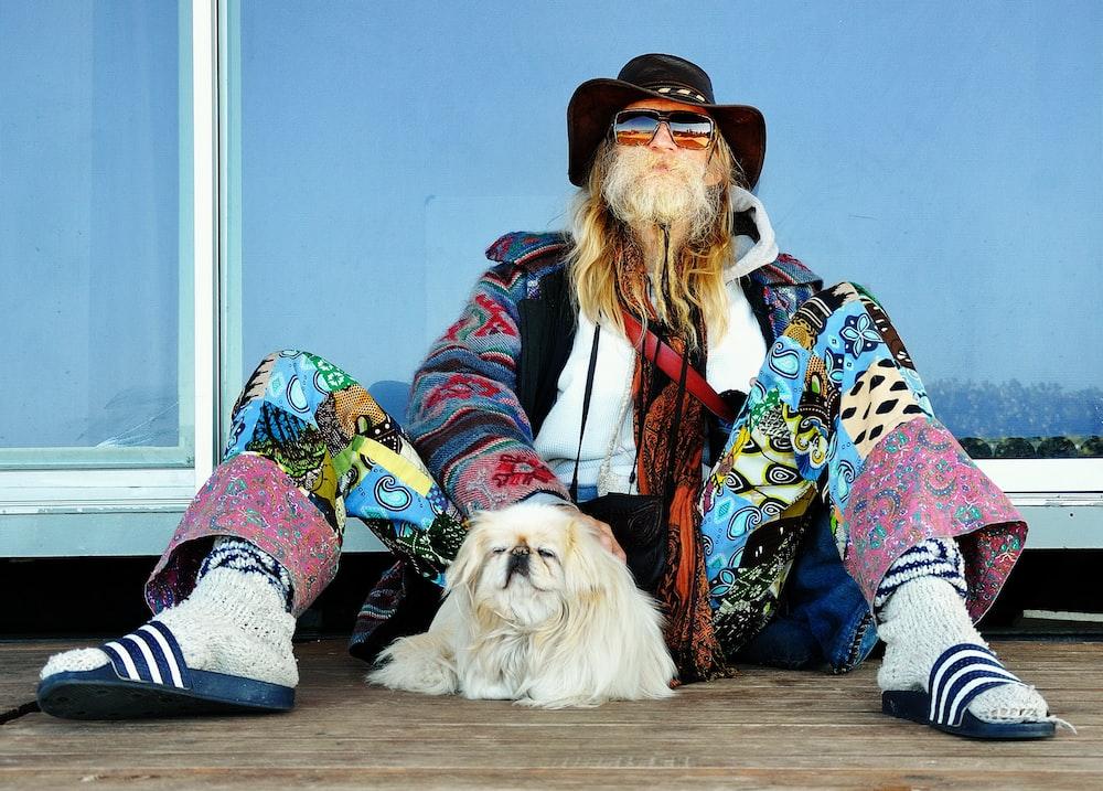 man sitting on floor beside dog during daytime