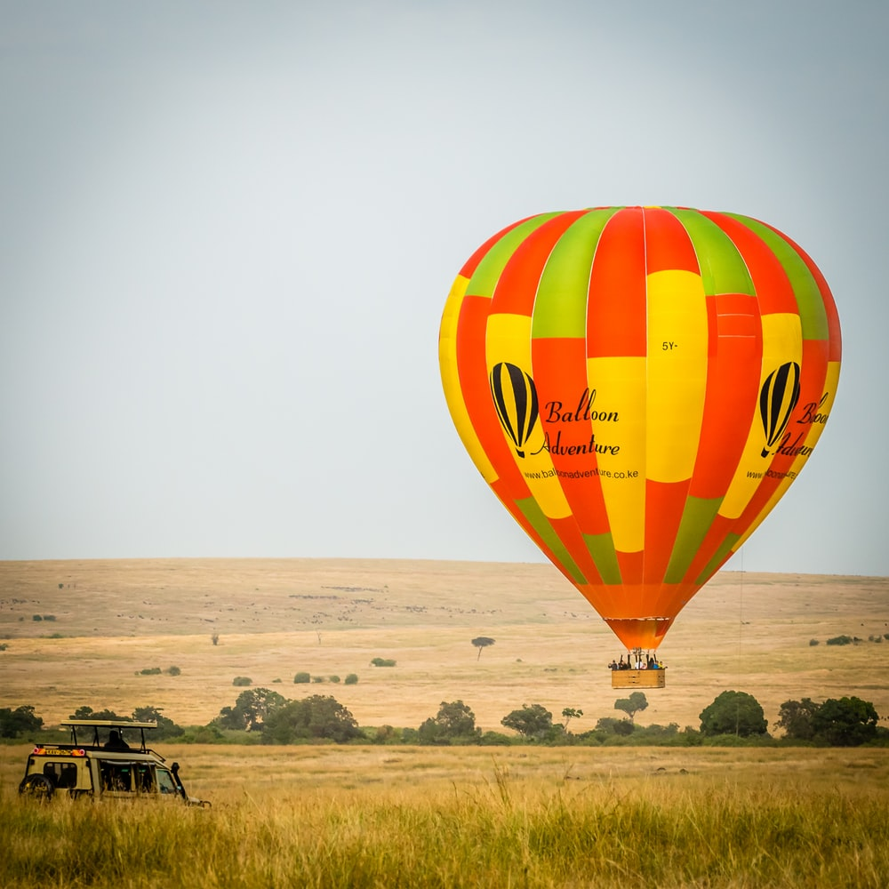 vehicle near hot air balloon under gray sky during daytime