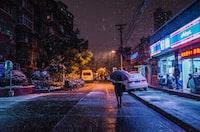 person using umbrella walking on road