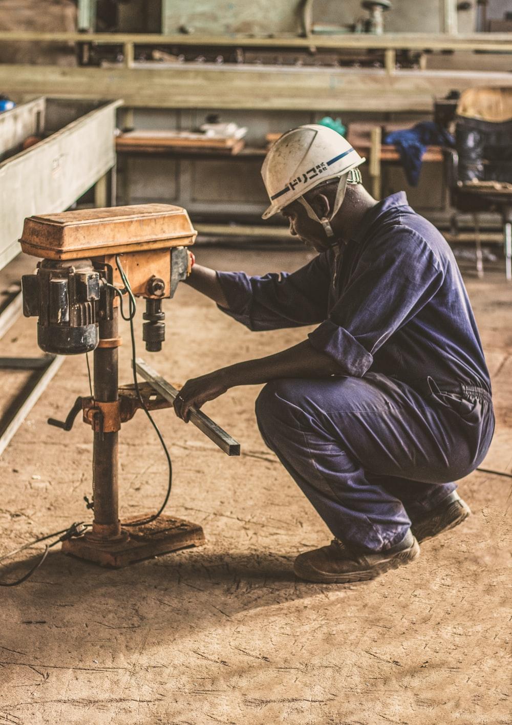 man wearing white hard hat operating brown drill press