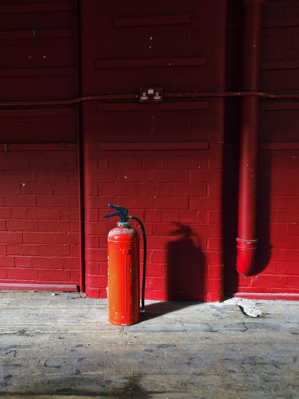 red fire extinguisher near red wall
