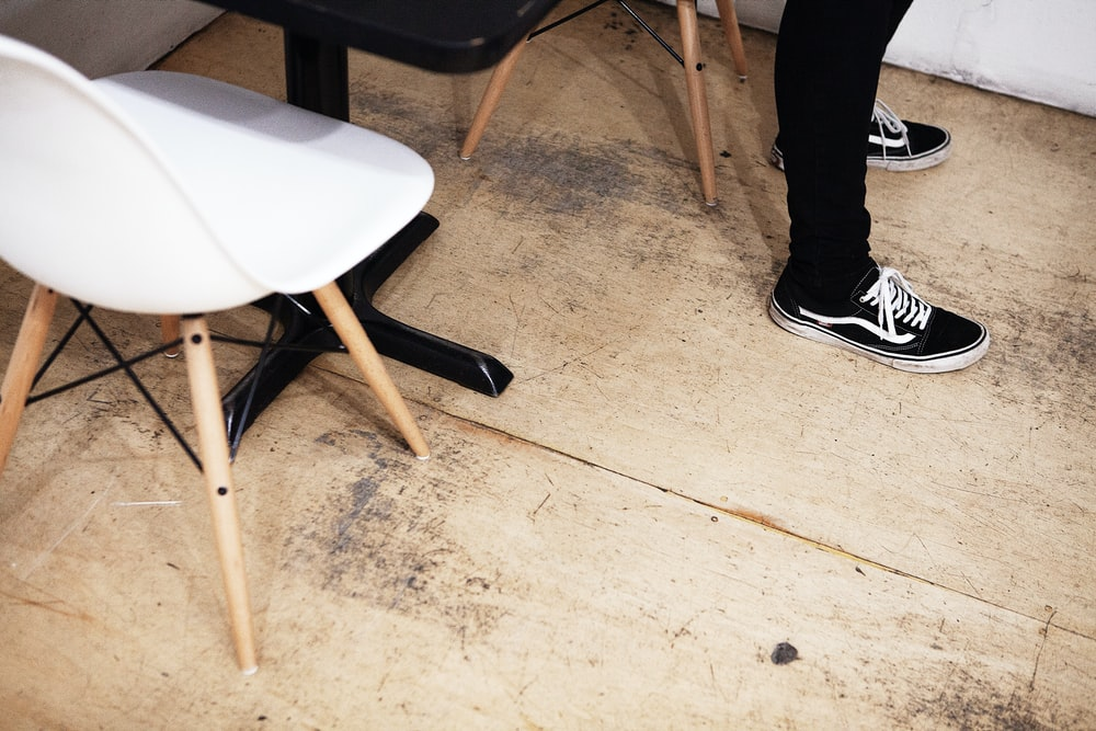 person standing on brown floor near table and chair