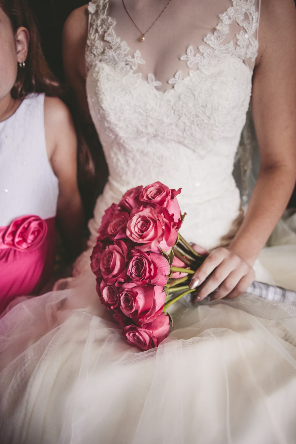 woman wearing white floral wedding dress holding bouquet of rose