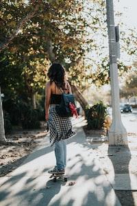 woman riding on skateboard on sidewalk