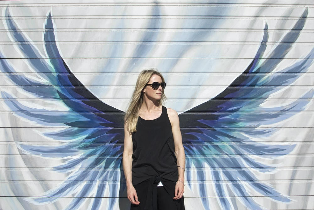 woman taking photo near wings painted wall