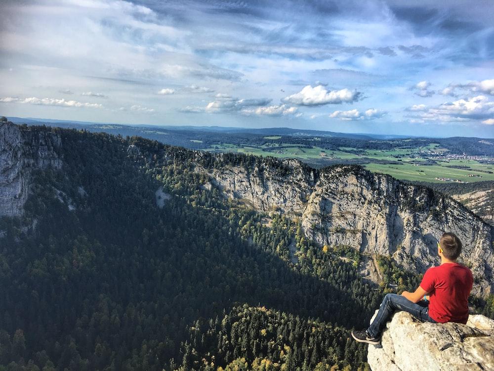 man sitting on brown rock during daytime