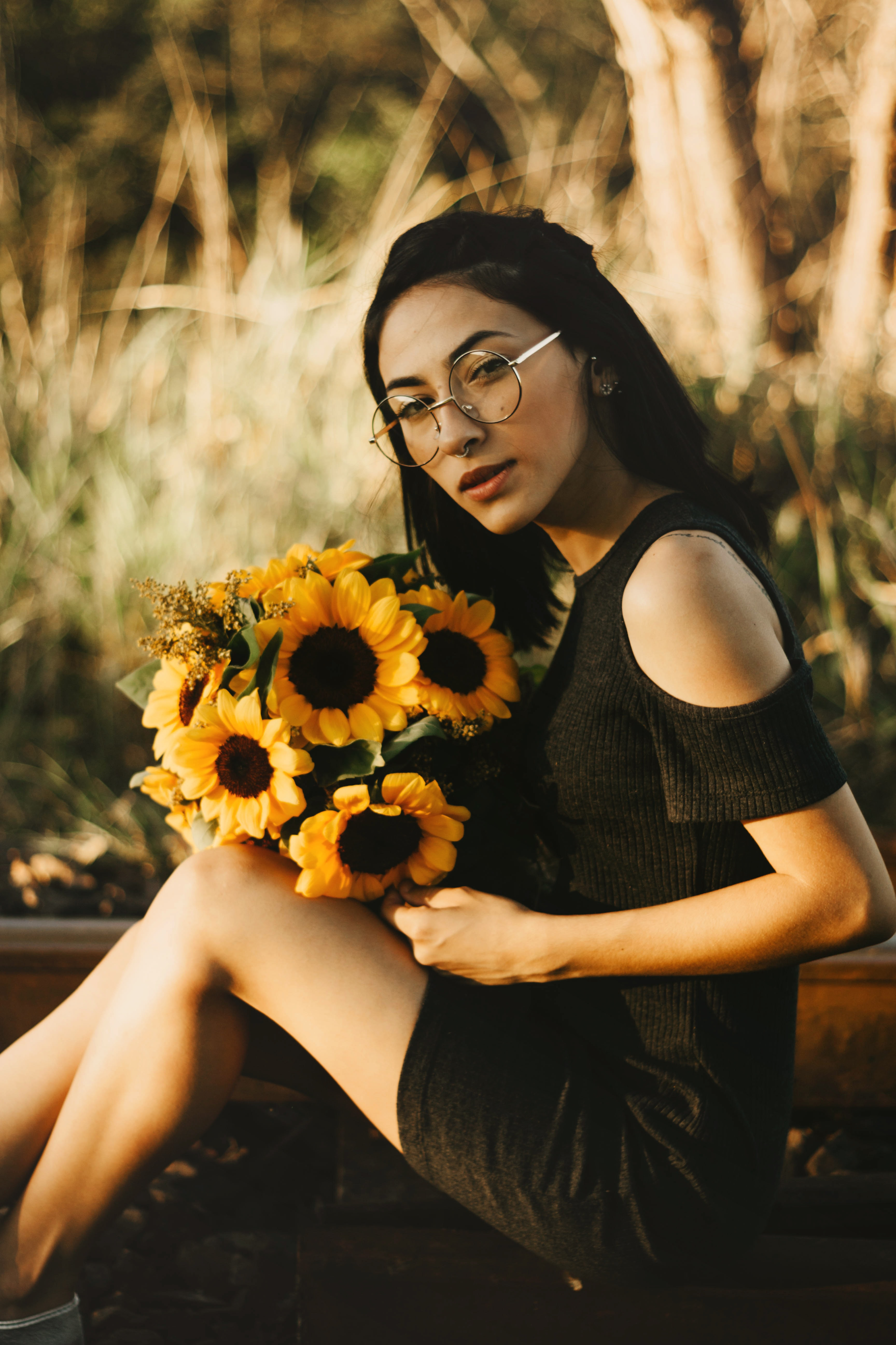 woman sitting on wood while holding sunflowers