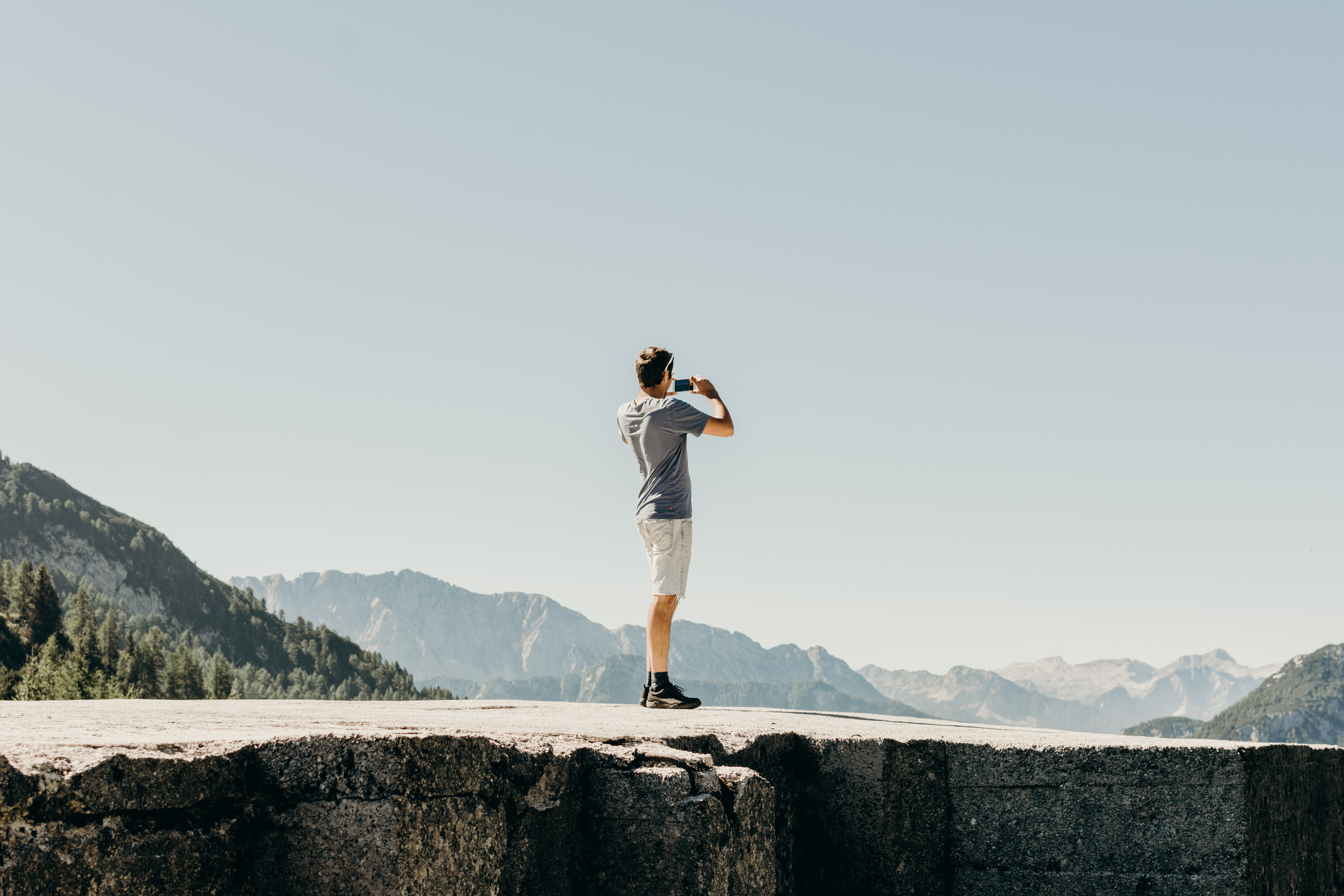 man standing on gray concrete cliff