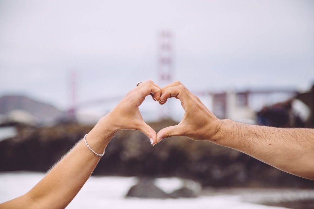 couple forming heart using their hands in focus photography