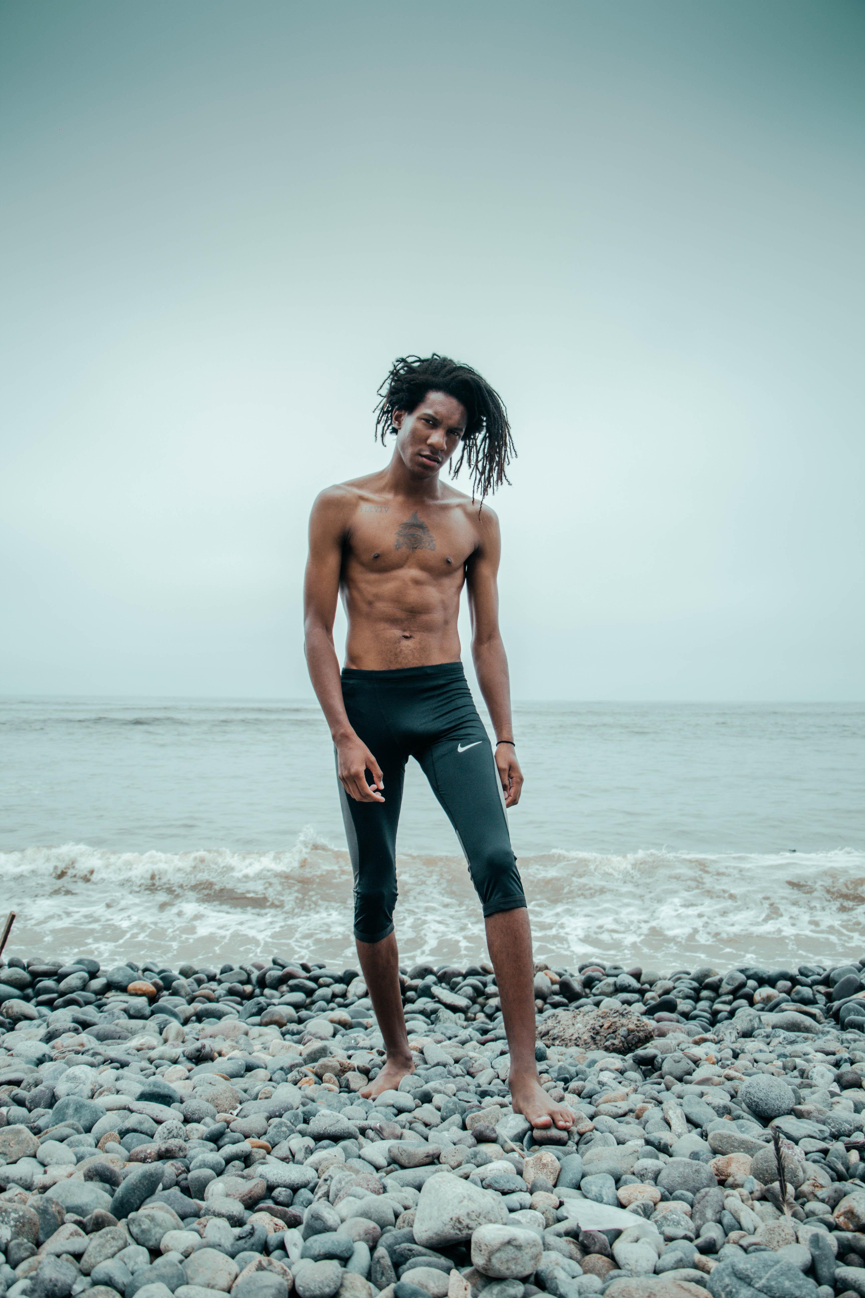 man standing wearing black Nike shorts near the beach