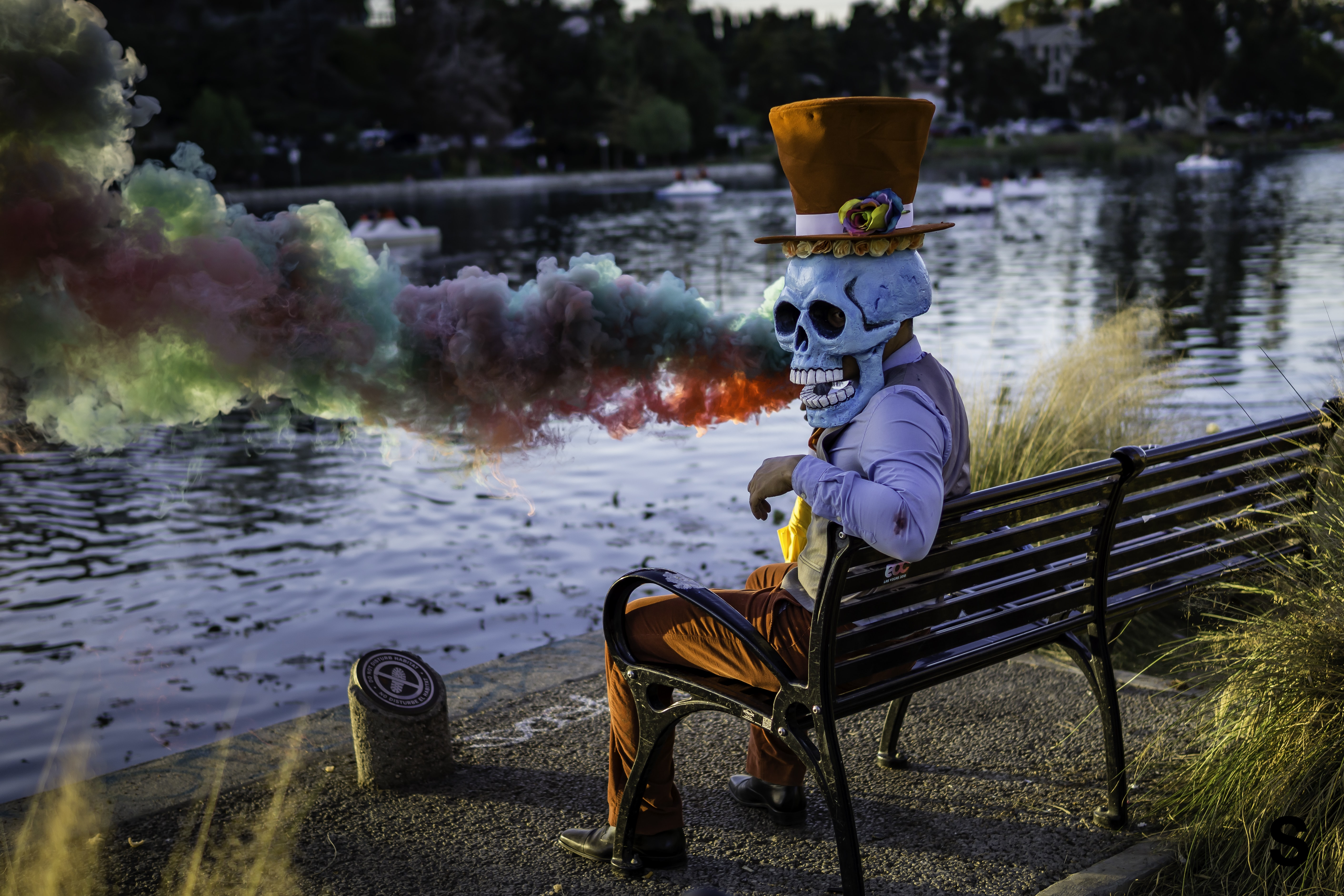 person wearing skull mask costume sitting on bench