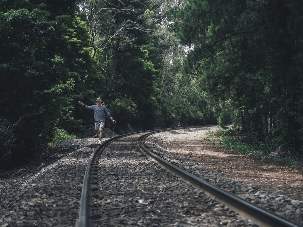 person walking through train rails between forest during daytime