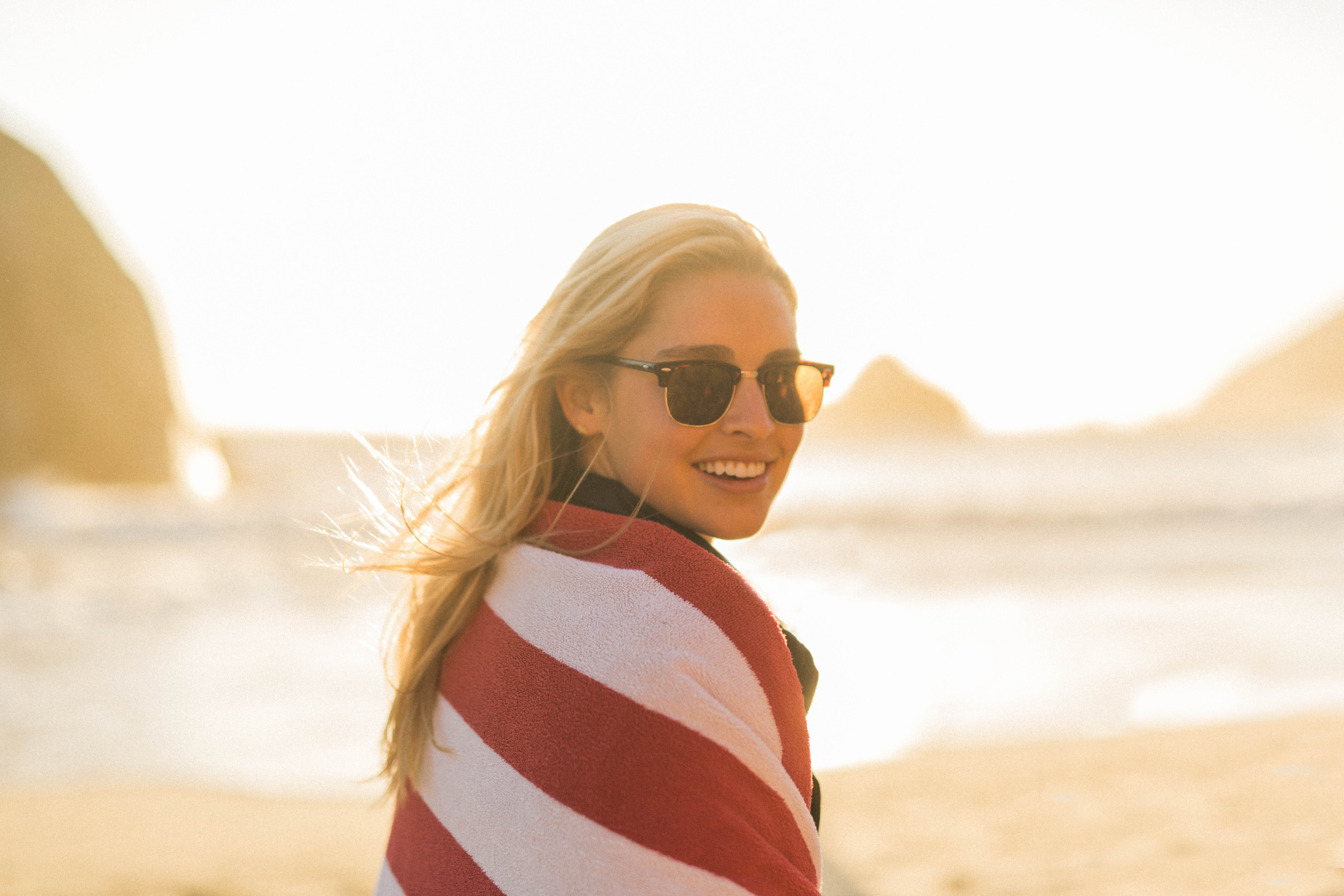 woman wearing black sunglasses with red and white striped blanket cover standing near seashore during daytime