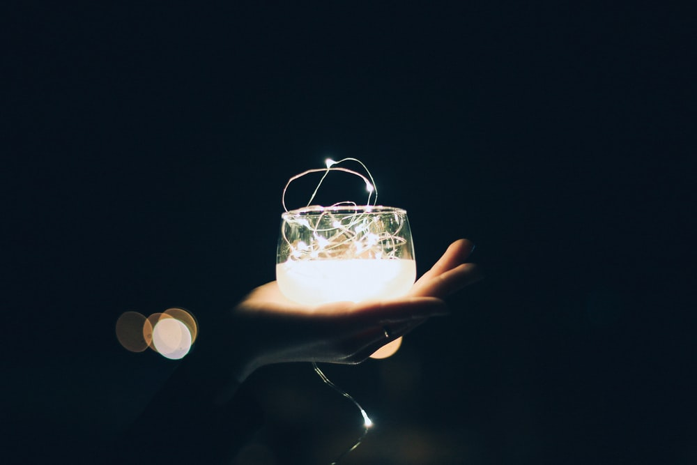 person holding clear glass candle light holder