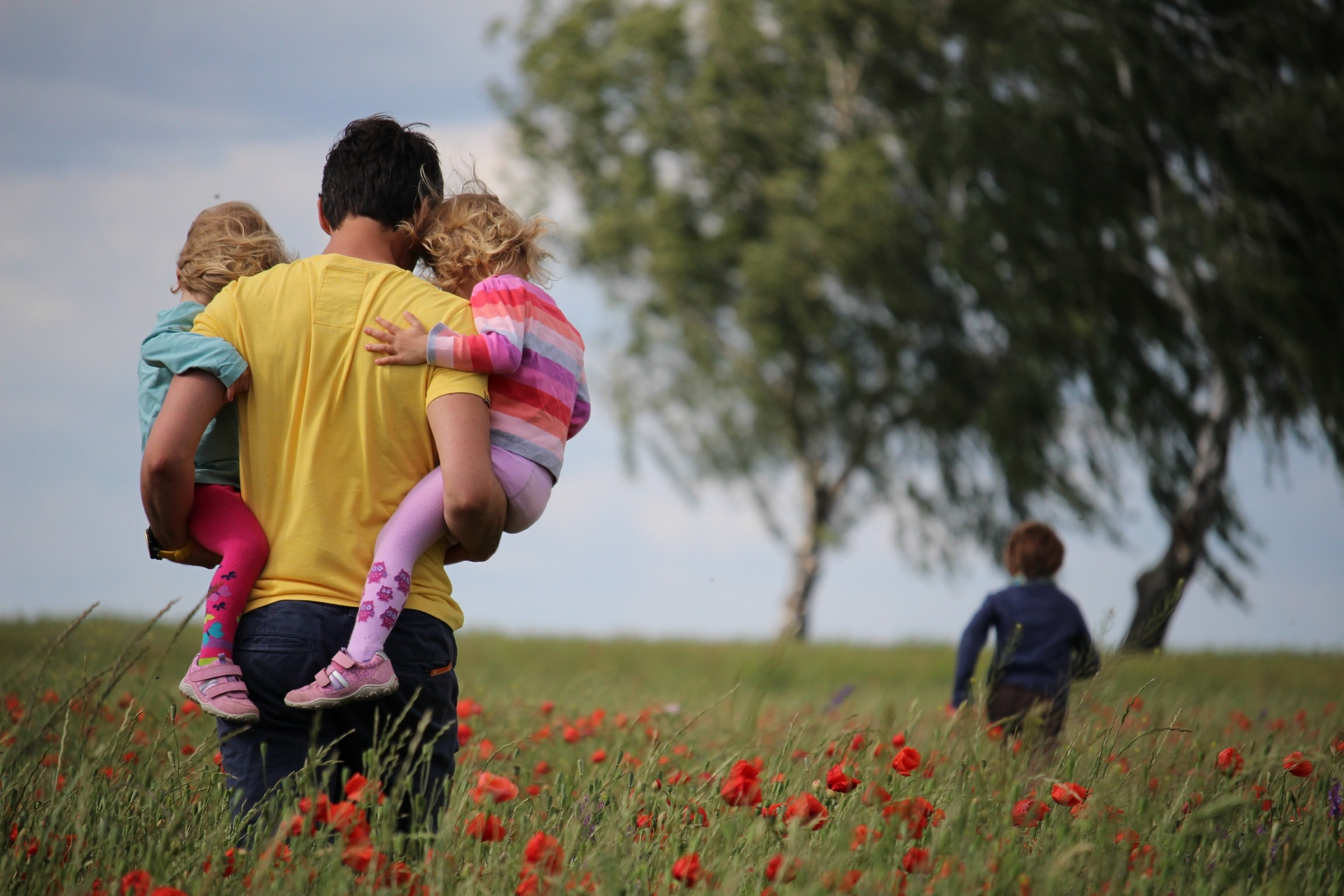 man carrying to girls on field of red petaled flower