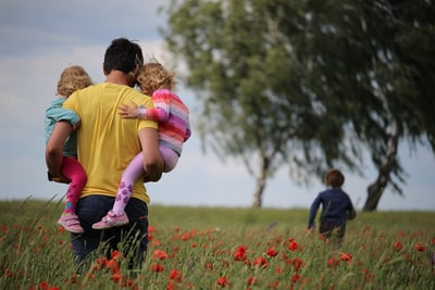 man carrying to girls on field of red petaled flower father's day teams background