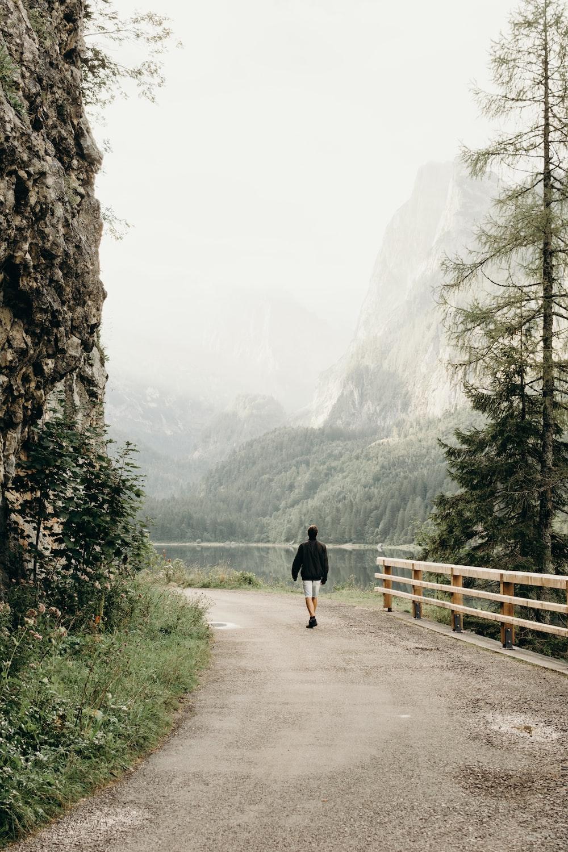 person wearing black jacket walking on road near the tree