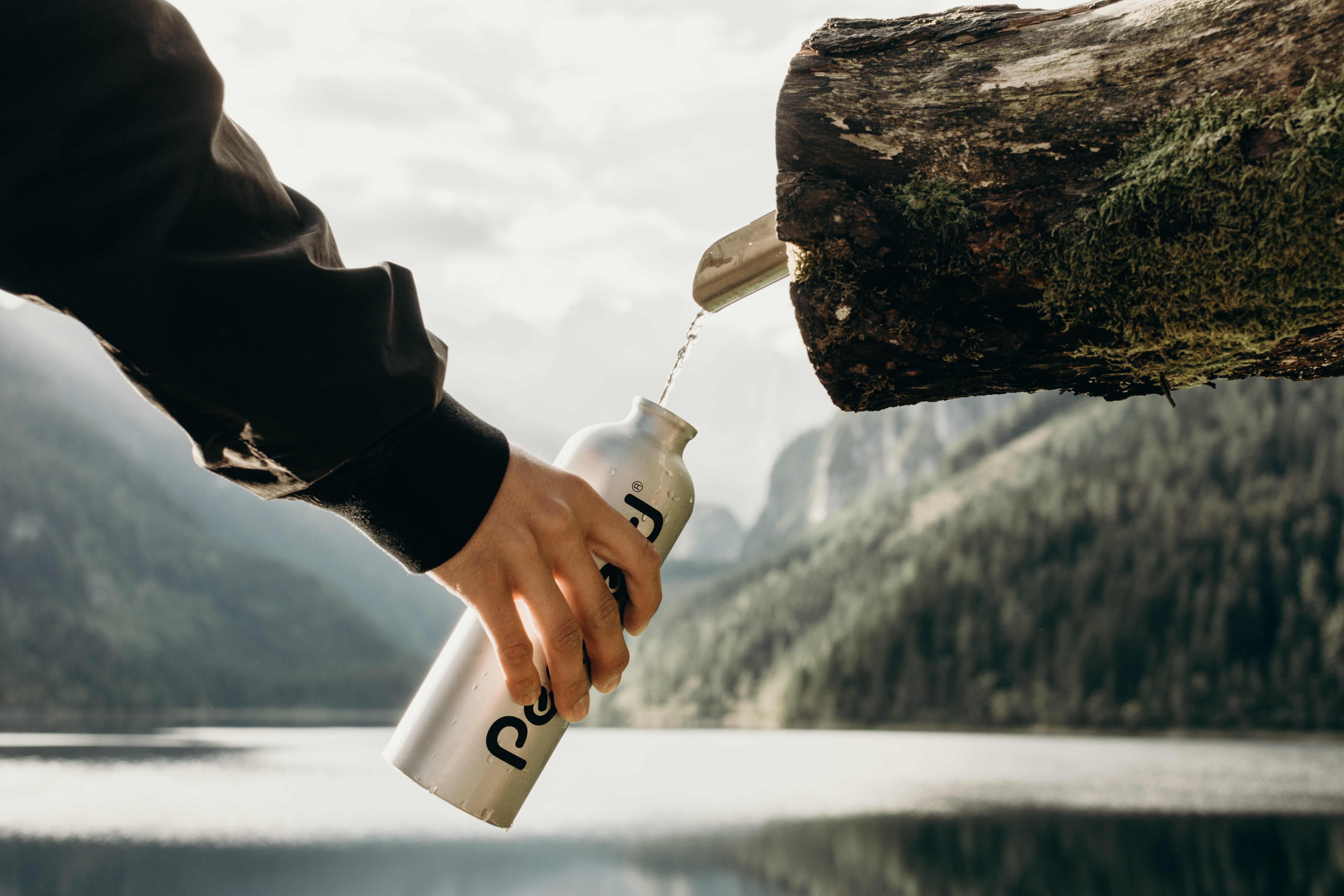 person holding gray sports bottle near nozzle