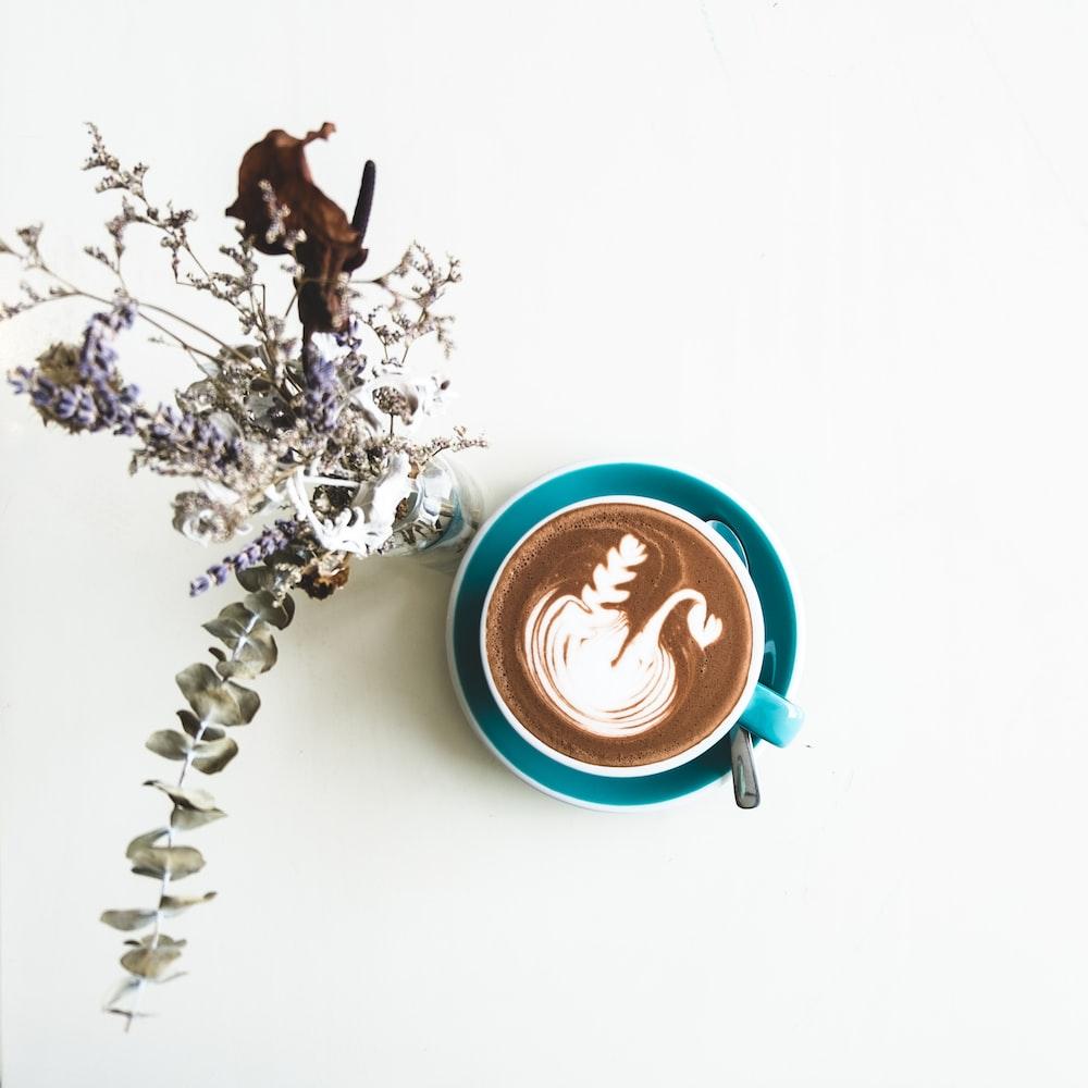 chocolate latte in cup beside flowers in vase