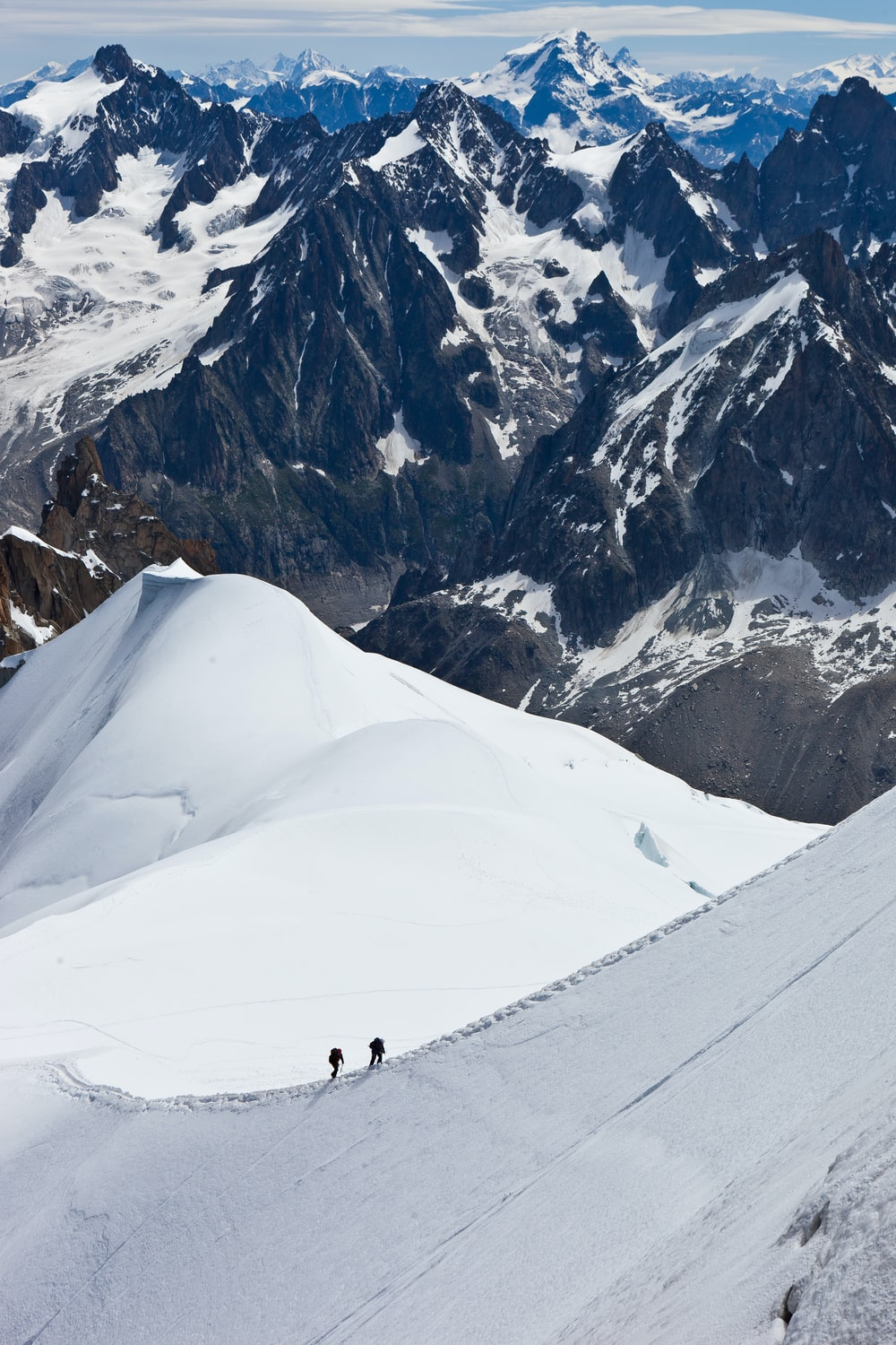 aerial view of two people hiking up snowy mountain