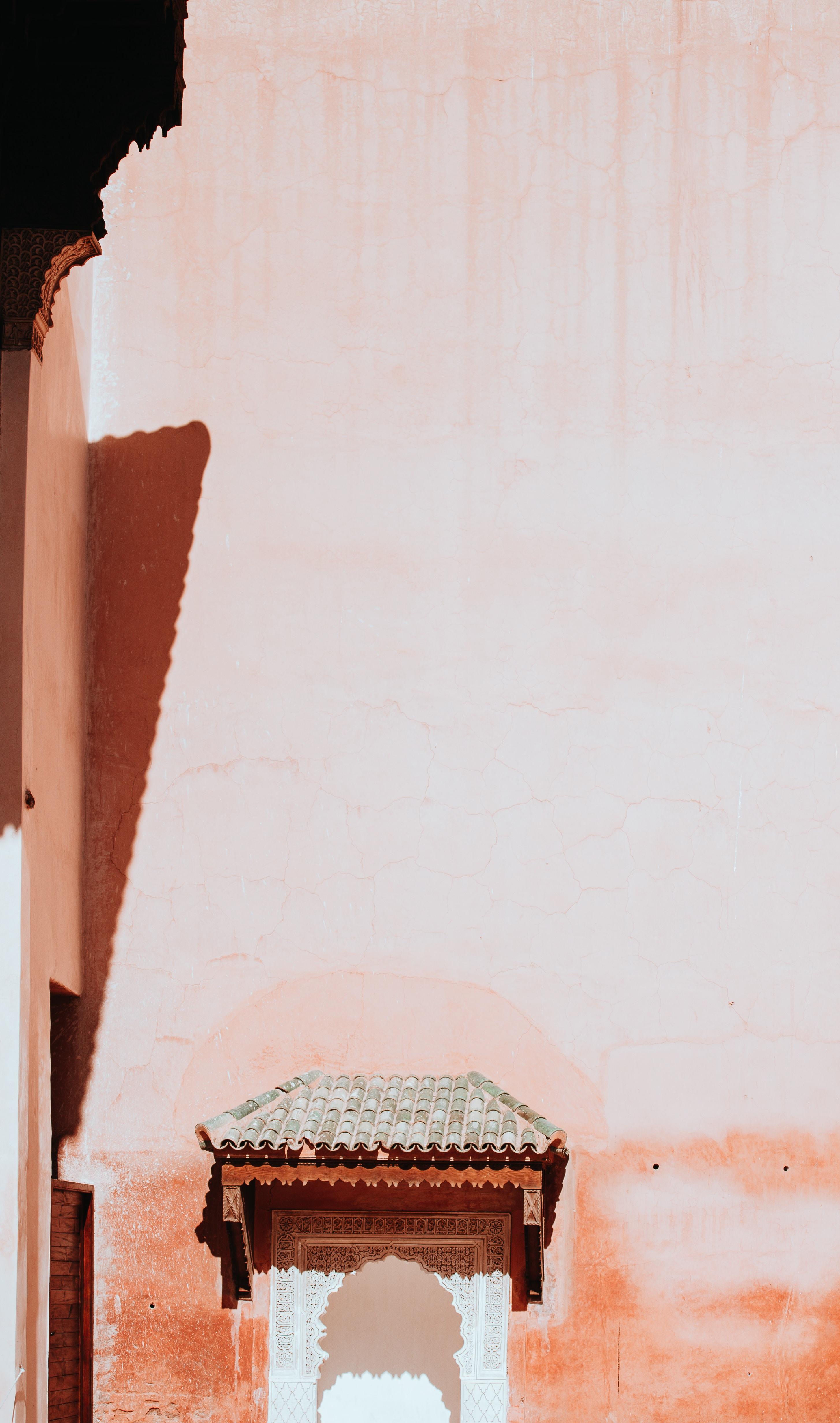 grey brick roof beside beige wall