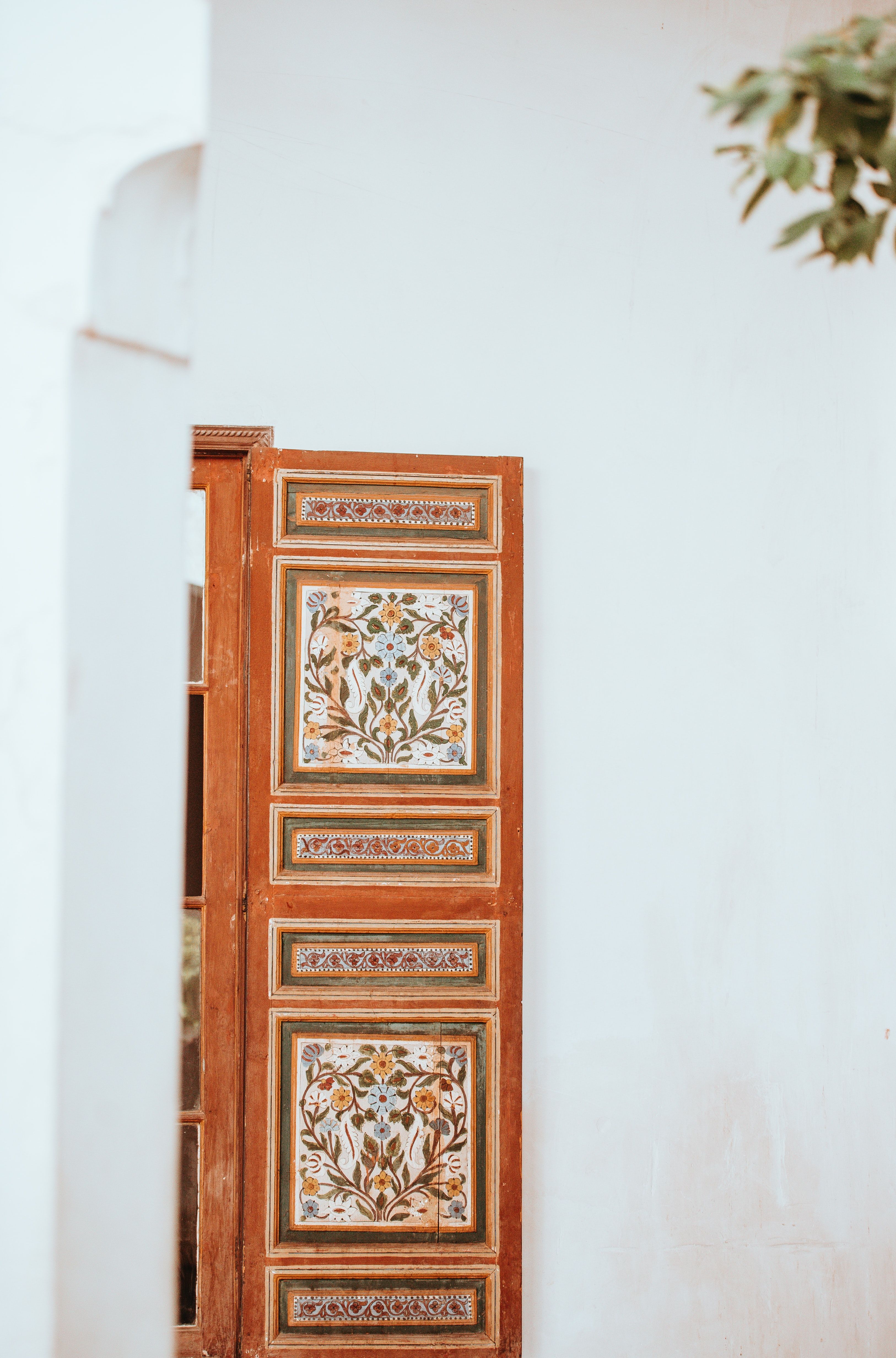 brown and white floral wooden cabinet near white wall