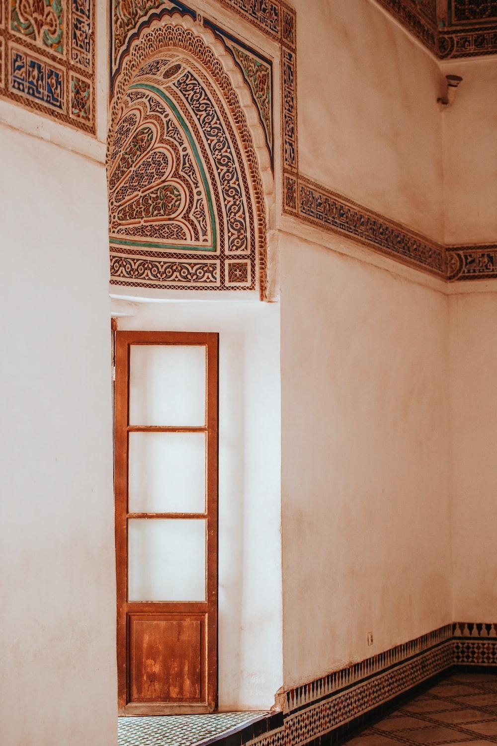 white wooden door beside concrete wall