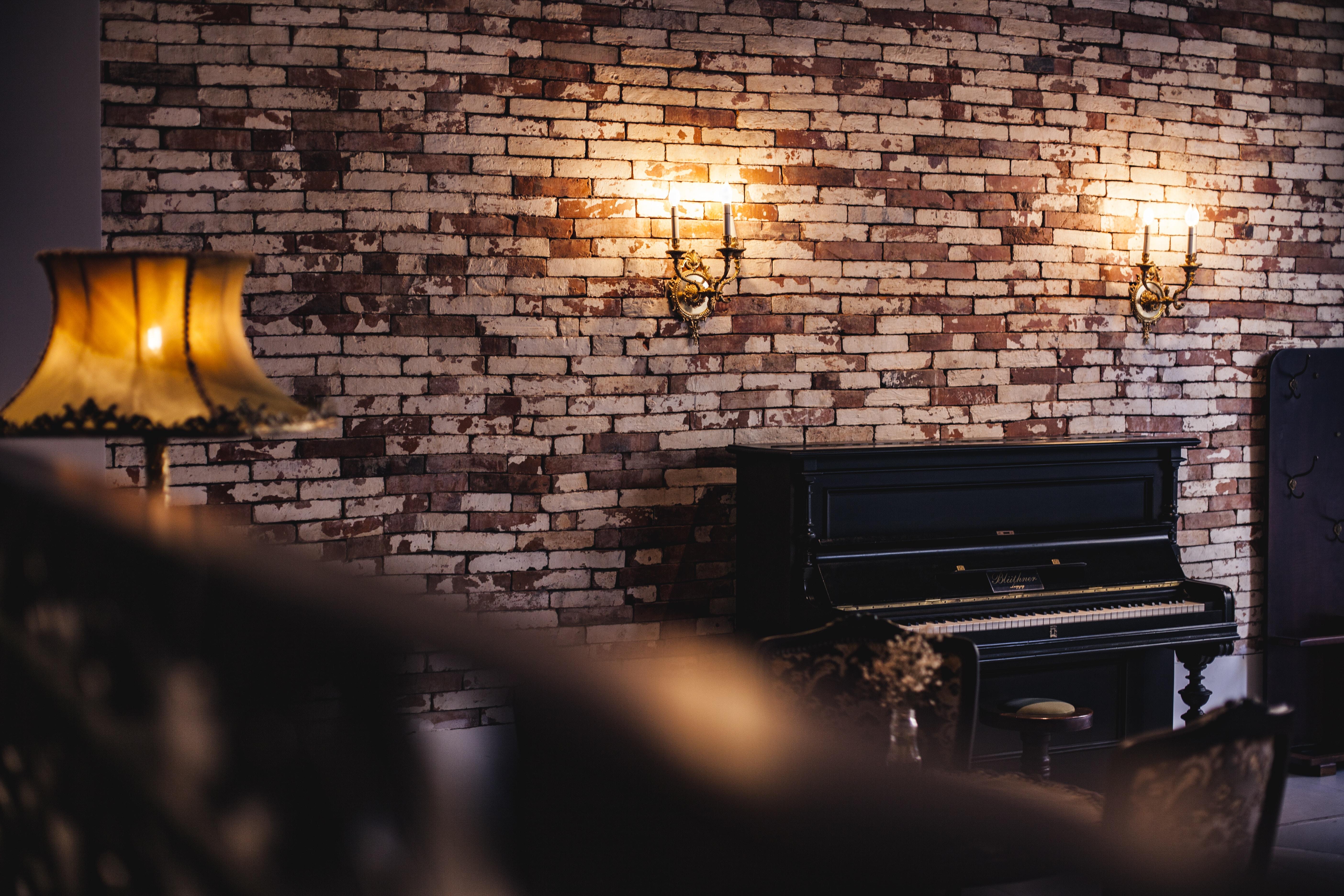 black upright piano near brown lampshade