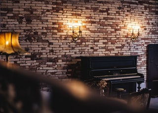 black upright piano near brown lampshade