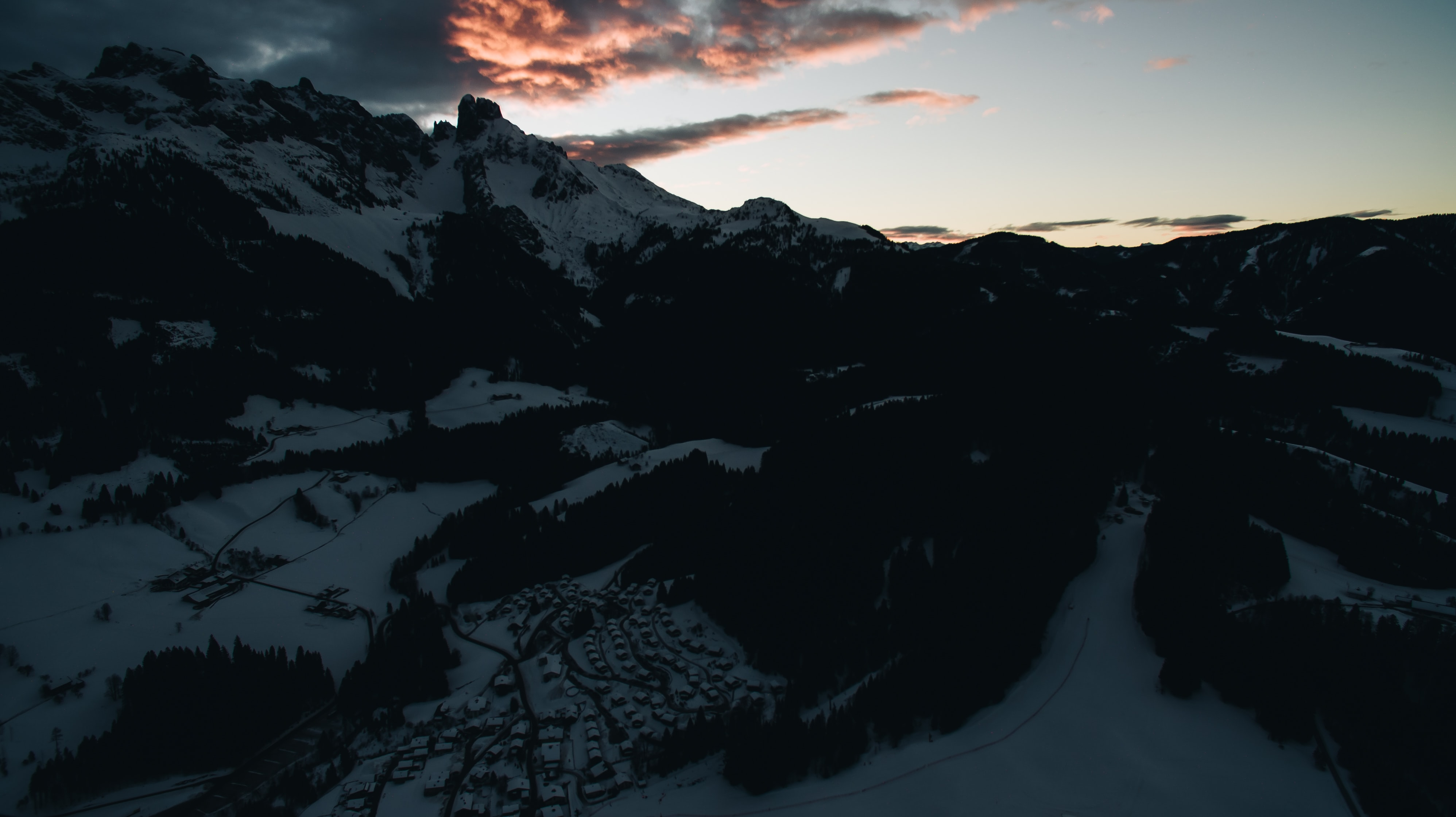 aerial view of snow covered mountain under clouds