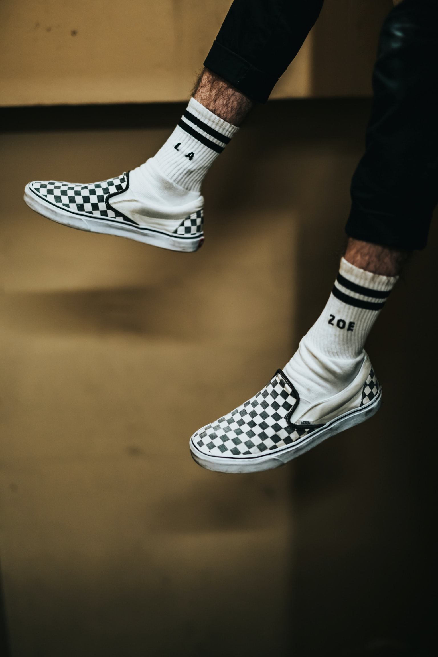 person wearing white-and-black checked slip-on shoes