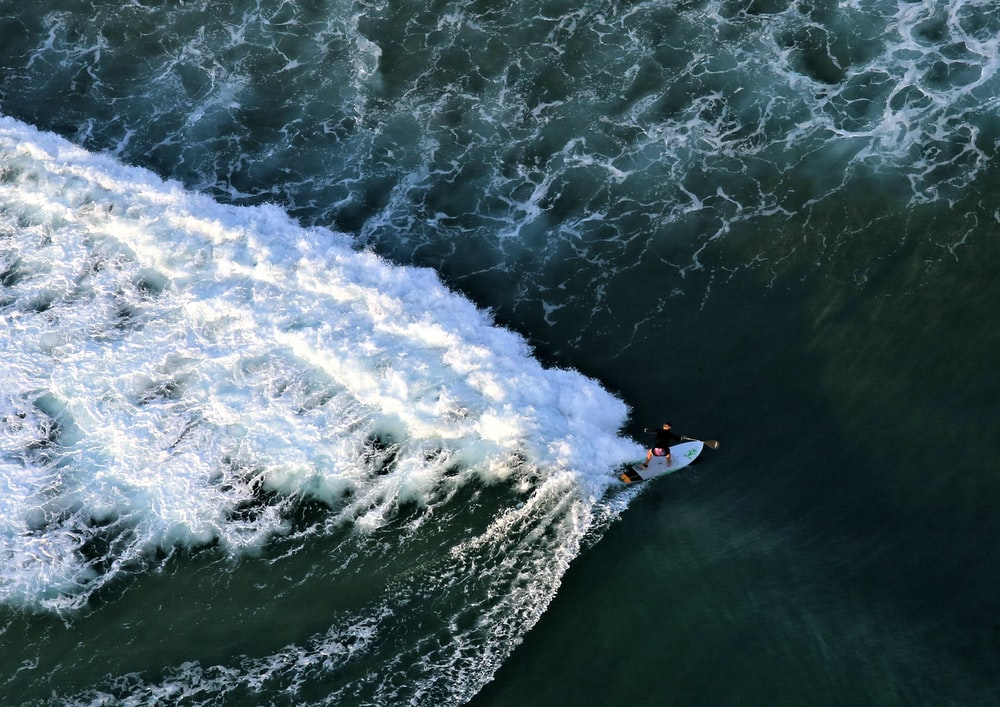 top view photography of man beside surfboard