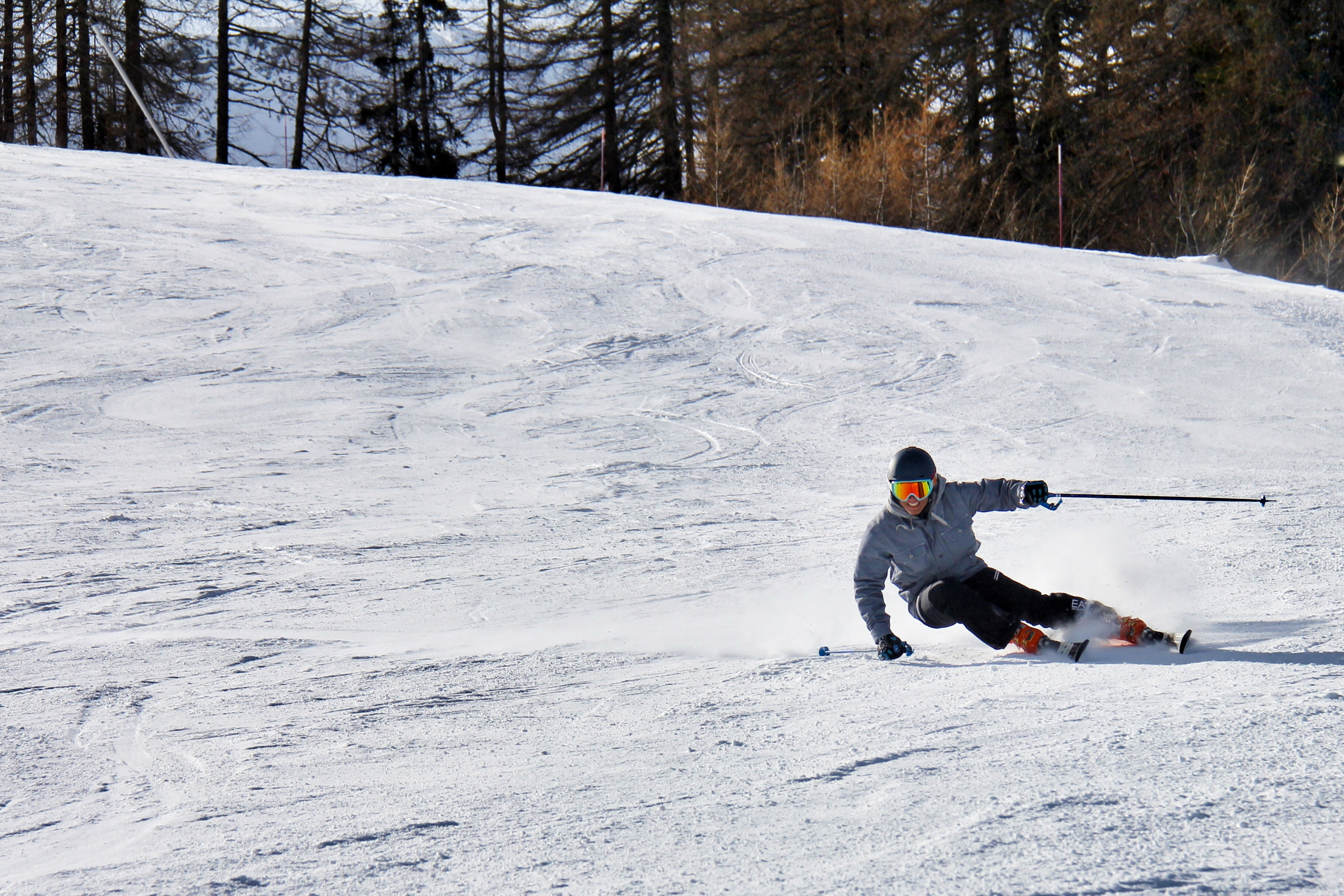 person in gray jacket and black pants skiing downhill
