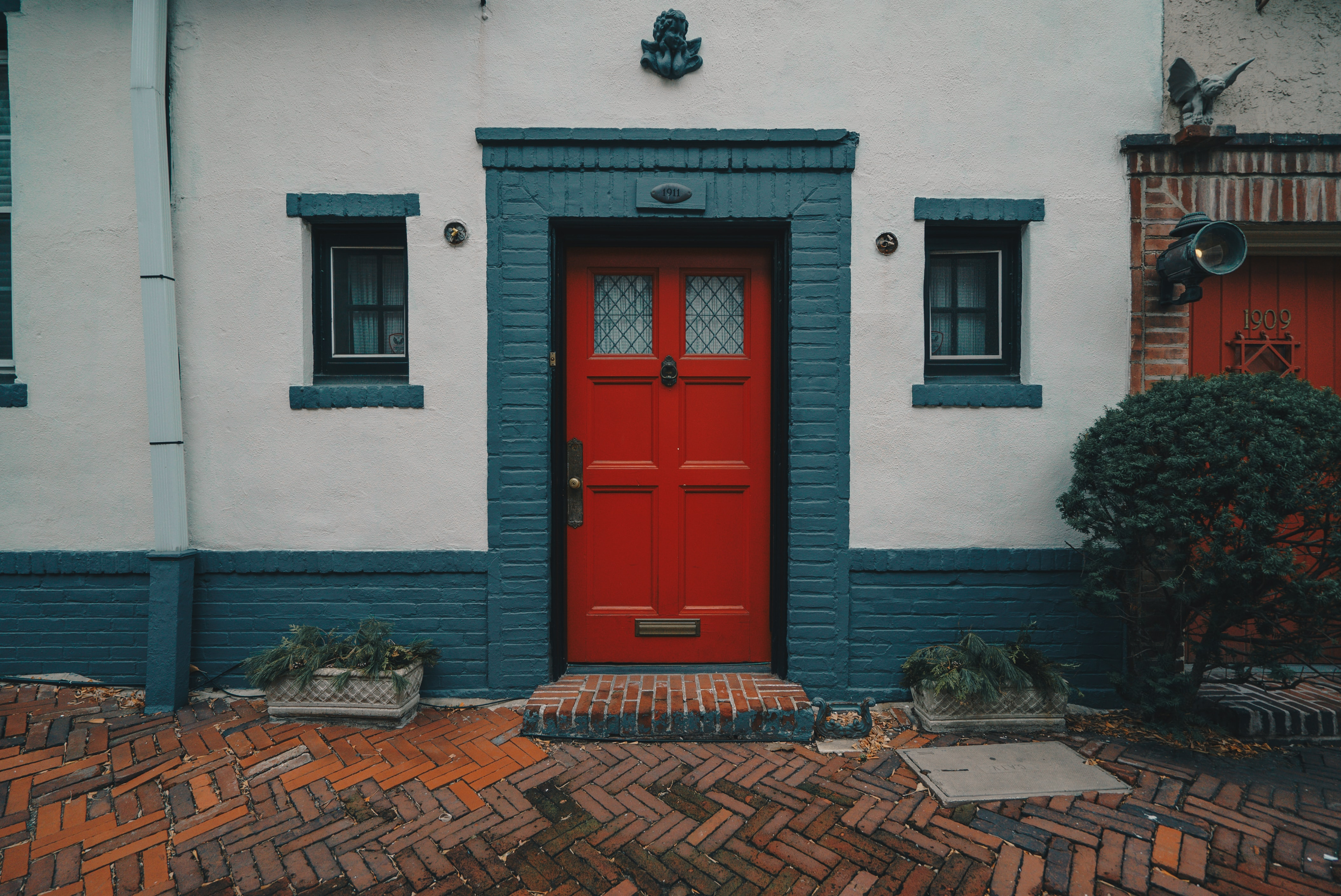 red wooden door on white and blue concrete house
