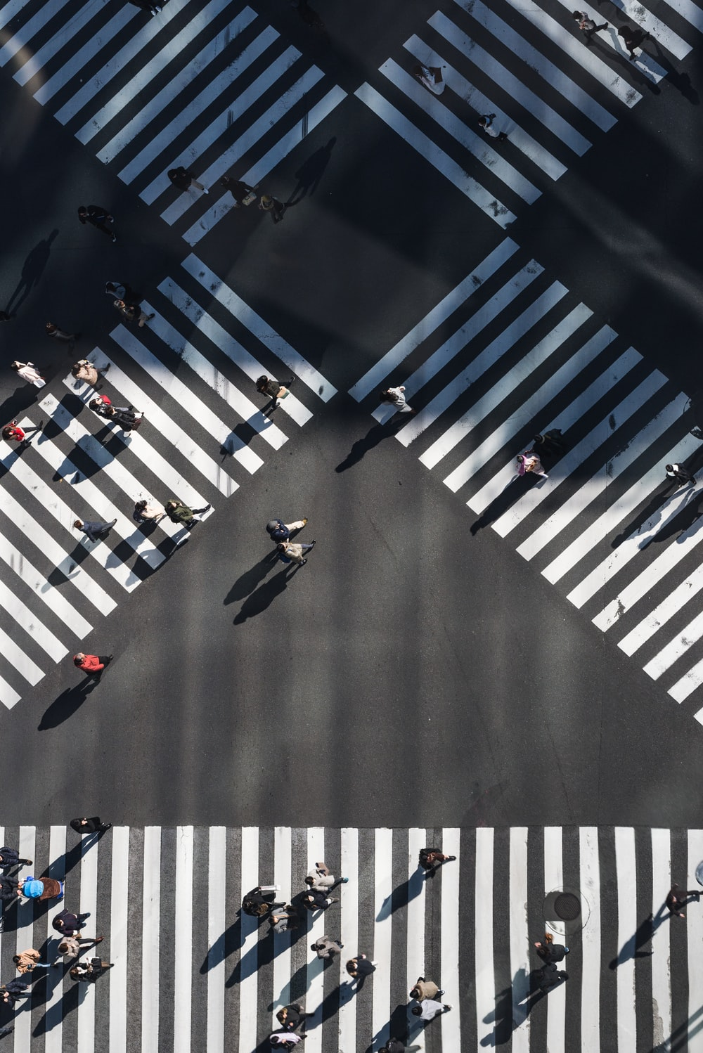 aerial photography of people walking in the intersection street during daytime