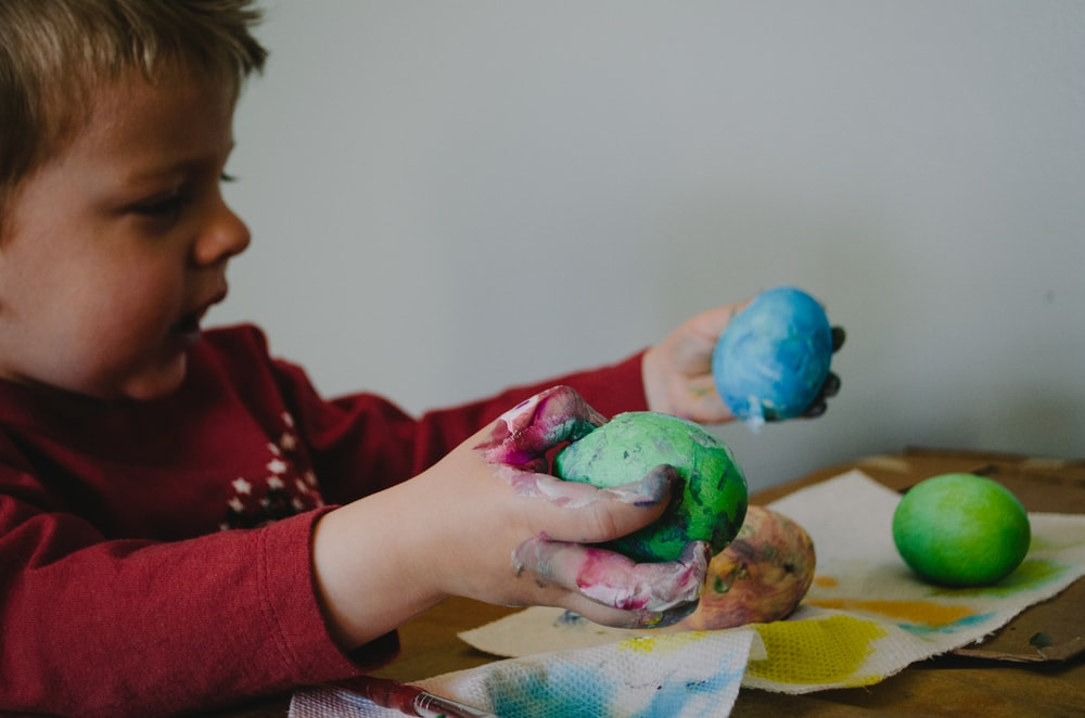 boy holding blue and green painted egg shells