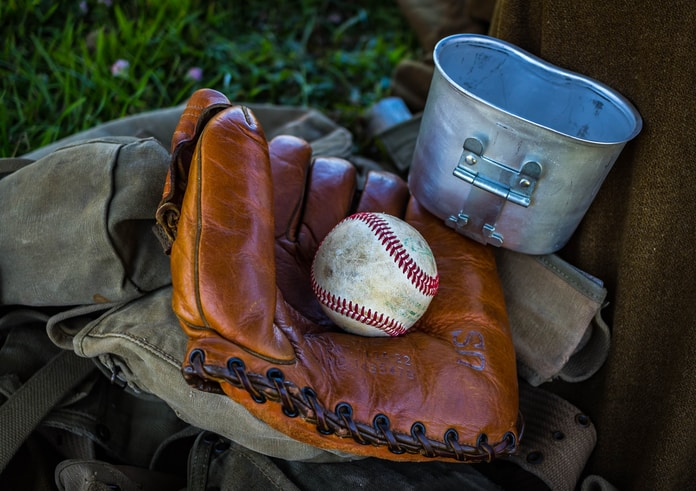 brown leather baseball mitt with baseball beside gray container and brown textile at daytime