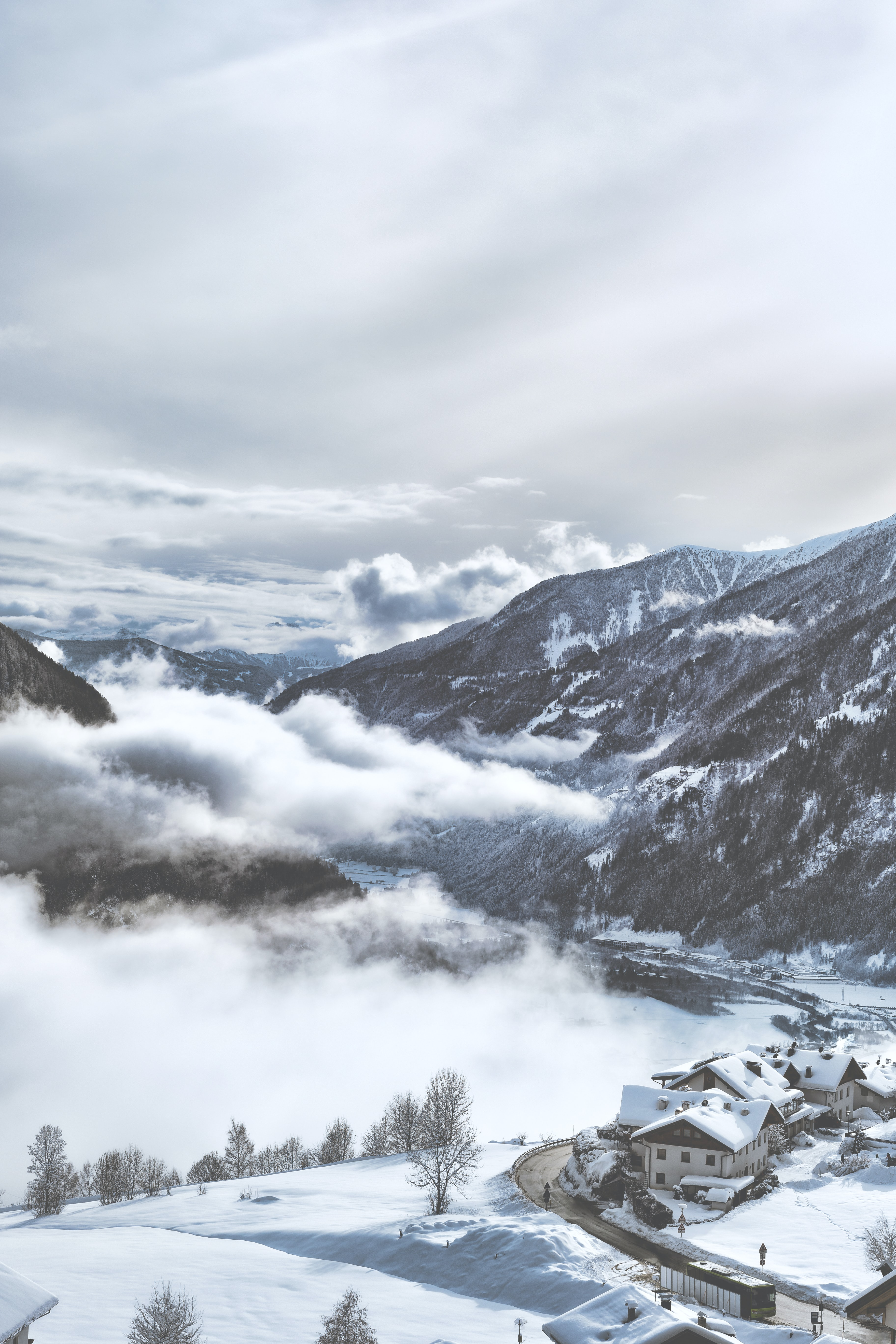 snow-covered village near mountains under white clouds during daytime