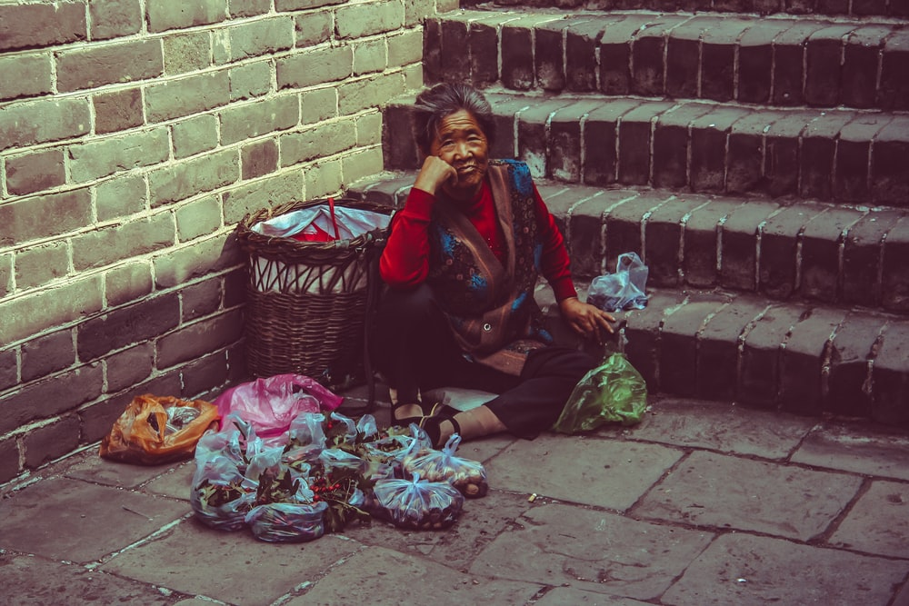 woman sitting on brown concrete ground beside brown wicker basket