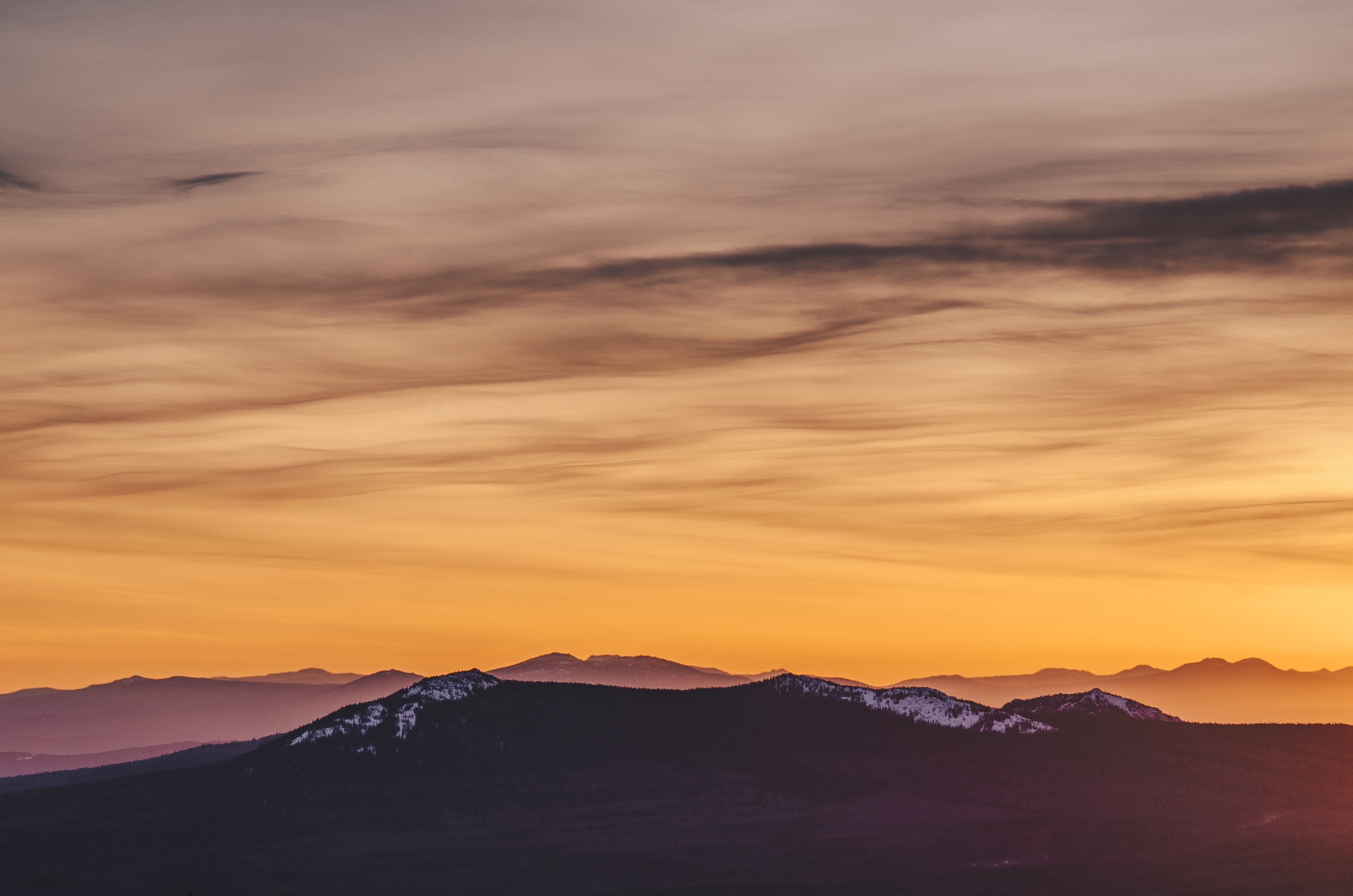 silhouette of mountain during yellow cloudy skies
