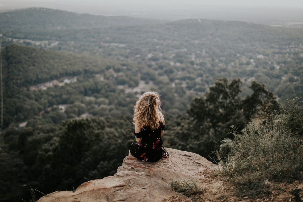 woman siting on cliff