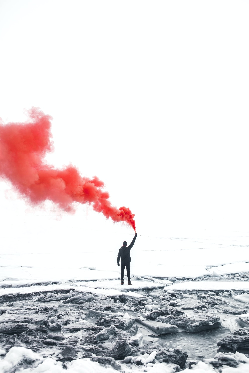 selective color photography of person holding orange gas smoke standing on snow